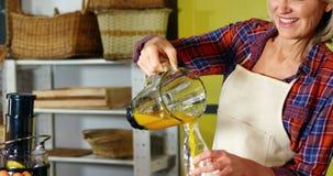 Frau, die Orangensaft in eine Flasche gießt stock video footage