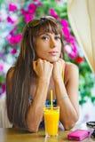 Frau, die Orangensaft im Café trinkt lizenzfreie stockfotografie