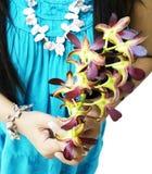 Frau, die Orchideenblumen hält Lizenzfreie Stockfotos