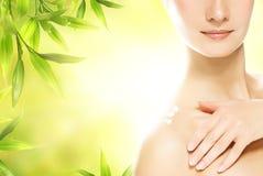 Frau, die organische Kosmetik an ihrer Haut aufträgt Stockbild