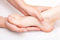 Frau, die osteopathic Behandlung ihres Fußgelenkes bekommt Stockfotos
