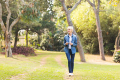 Frau, die am Park geht lizenzfreie stockbilder