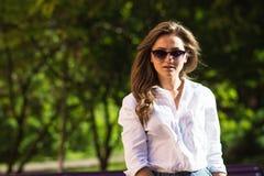 Frau, die am Park stillsteht Mädchen in der Sonnenbrille, Sommerporträt im Freien Stockbild