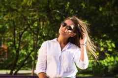 Frau, die am Park stillsteht Mädchen in der Sonnenbrille, Sommerporträt im Freien Stockfotografie