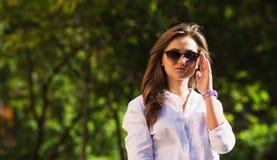 Frau, die am Park stillsteht Mädchen in der Sonnenbrille, Sommerporträt im Freien Lizenzfreie Stockfotografie