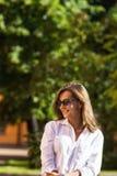 Frau, die am Park stillsteht Mädchen in der Sonnenbrille, Sommerporträt im Freien Lizenzfreies Stockfoto
