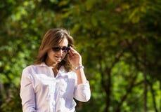 Frau, die am Park stillsteht Mädchen in der Sonnenbrille, Sommerporträt im Freien Lizenzfreie Stockfotos