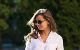 Frau, die am Park stillsteht Mädchen in der Sonnenbrille, Sommerporträt im Freien Lizenzfreie Stockbilder
