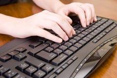 Frau, die an PC-Tastatur und -maus arbeitet. Lizenzfreie Stockfotos