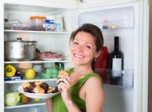 Frau, die Pfannkuchen nahe Kühlschrank isst Stockfotos