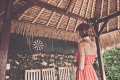 Frau, die Pfeile im tropischen Café von Nusa Lembongan, Bali, Indonesien spielt lizenzfreie stockfotos
