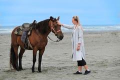 Frau, die Pferd auf Strand durch das Meer tappt lizenzfreie stockfotos