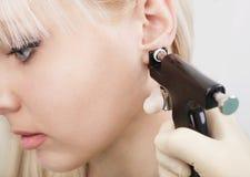 Frau, die piercing Prozess des Ohrs mit spezieller Ausrüstung hat Lizenzfreie Stockbilder