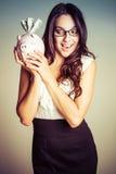 Frau, die Piggy Querneigung anhält lizenzfreie stockbilder