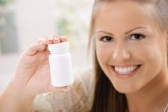 Frau, die Pilleflasche zeigt Stockfoto
