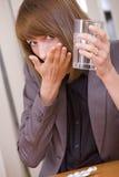 Frau, die Pillen durch Arbeit nimmt Lizenzfreies Stockfoto