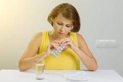 Frau, die Pillen in ihrer Hand, Pillen einnehmend hält Stockfotografie