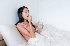 Frau, die Pillen und Getränk des Wassers auf Bett nimmt Stockbild