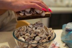 Frau, die Pilze hackt lizenzfreie stockfotografie