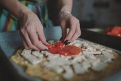 Frau, die Pizza an der Küche kocht Stockbild