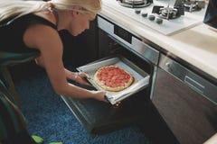 Frau, die Pizza an der Küche kocht Lizenzfreie Stockfotografie