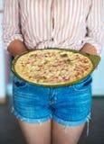 Frau, die Pizza hält lizenzfreie stockbilder