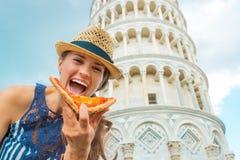 Frau, die Pizza vor Turm von Pisa isst Stockfotografie