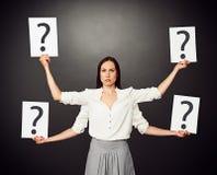 Frau, die Plakate mit Fragezeichen hält Stockfotos