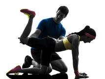 Frau, die Plankenpositions-Eignungstraining mit Manntrainer ausübt Lizenzfreie Stockfotografie