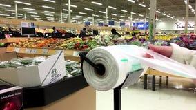 Frau, die Plastiktasche für kaufendes Lebensmittel nimmt stock footage