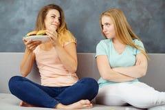 Frau, die Platte mit Burgern weg ihres Freunds nimmt lizenzfreie stockfotos