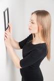 Frau, die Platz für Bild auf der Wand wählt Lizenzfreie Stockfotografie