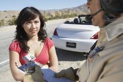 Frau, die Polizeibeamten Writing On Clipboard betrachtet Stockbilder