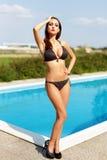 Frau, die am Pool aufwirft Stockbild