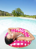 Frau, die in Pool mit den Augen geschlossen schwimmt Stockfoto
