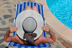 Frau, die am Pool sich entspannt Lizenzfreie Stockfotografie