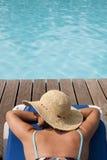 Frau, die am Pool sich entspannt Stockbilder