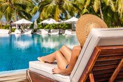 Frau, die am Poolside sich entspannt stockfotos