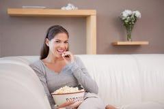 Frau, die Popcorn beim Überwachen des Films isst lizenzfreies stockfoto