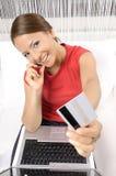 Frau, die Produkt unter Verwendung ihrer Laptop-Computers kauft Stockbilder