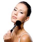 Frau, die Puder auf Stirn mit Pinsel anwendet Stockfoto