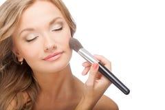 Frau, die Pulver auf Gesicht anwendet Stockbild