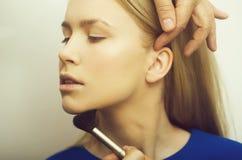 Frau, die Pulver auf Gesicht mit Make-upbürste erhält stockfotografie