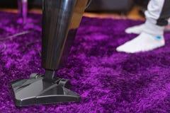 Frau, die purpurroten Teppich mit modernem Staubsauger im Wohnzimmer säubert stockbild
