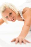 Frau, die Push-upsübungen auf weißem Fußboden tut stockfotografie