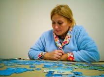 Frau, die Puzzlespiel im ruhigen Haus mit einem blauen Hausmantel tut stockfotos