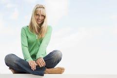 Frau, die quere mit Beinen versehene Außenseite sitzt Stockbild