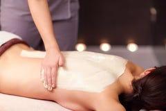 Frau, die Rückenmassage mit Sahne am Badekurort hat stockfoto