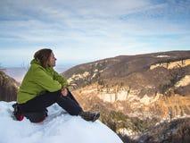 Frau, die am Rand der Klippe sitzt Stockfotografie