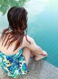 Frau, die am Rand des Swimmingpools sitzt Stockfotos